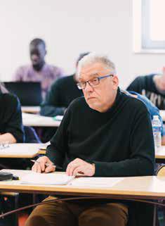 Homme assis à un bureau inscrit à UNIVA
